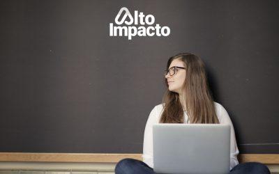 Mujer sentada en el piso con una computadora portátil. Detrás un cuadro negro.